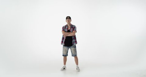 Young serious guy standing on white background looking at camera. Guy dressed in denim shorts, shirt and black cap, arms crossed on chest. Concept of confidence, dress style.