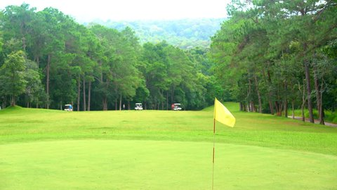 Golf sport concept, golf course beautiful for golfer playing in fairway and layout in forest on hills of vacation summer. Golf cart for transfer to other hole and yellow flag blowing and wind