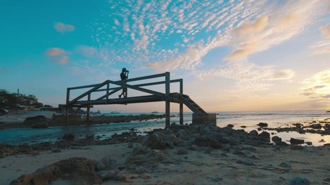 Photographer walking over wooden bridge taking pictures, Curacao