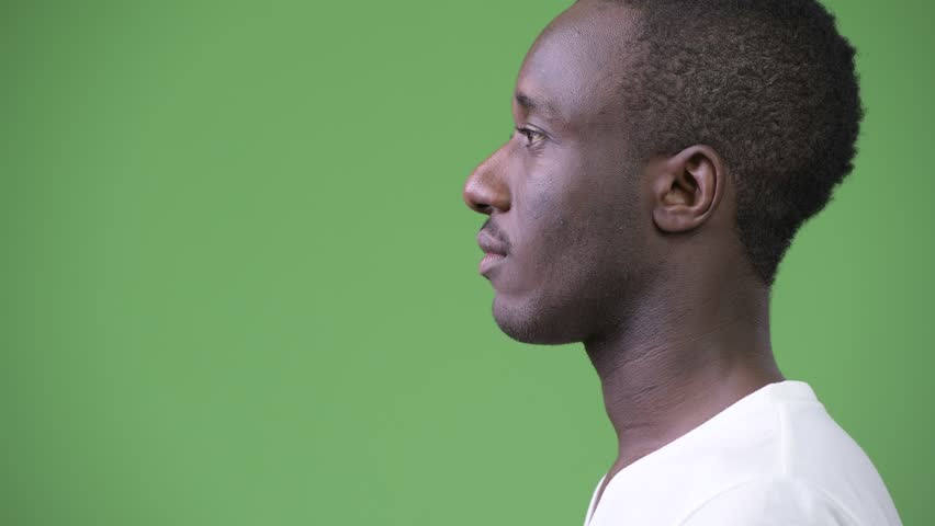 Profile view of young African man against green background | Shutterstock HD Video #1013382116