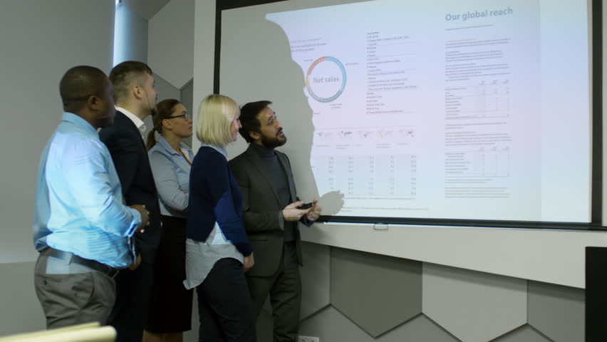 Asian entrepreneur showing presentation projected on whiteboard to multiethnic business team in dark office and explaining information on slide | Shutterstock HD Video #1013409986