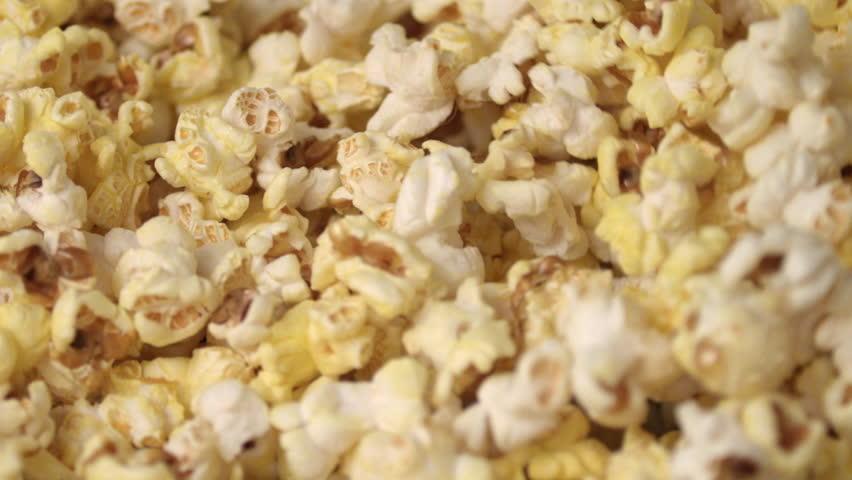 Fresh hot popcorn mixing in popcorn machine. Popcorn background. Close up of popcorn production in slow motion. Cinema pop corn background | Shutterstock HD Video #1013417696