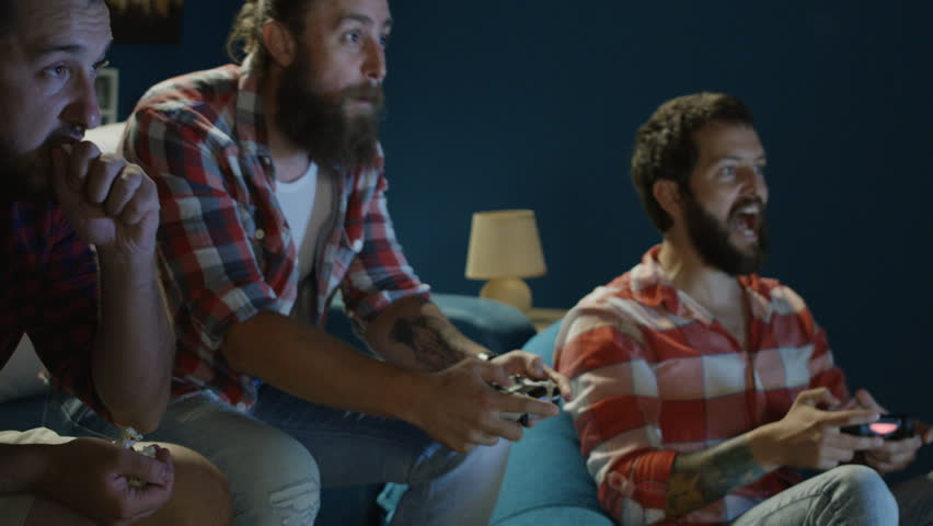Group of man chilling on sofa with gamepad and man mocking on other player when winning videogame round and having fun tease him | Shutterstock HD Video #1013428376