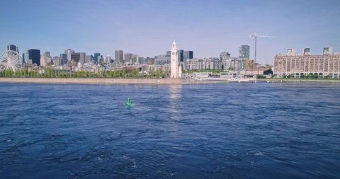 AERIAL: Flying over the old port, clock tower, city skyline and. Saint Lawrence river. Montreal, Canada