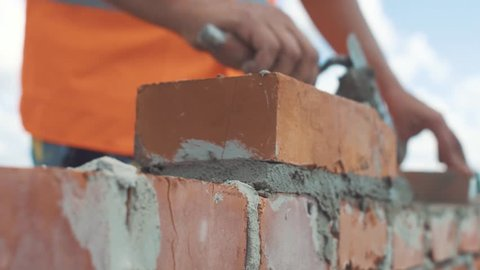 Handed shot of Bricklayer builds wall