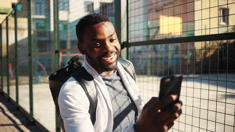 Good-looking student getting mobile phone from pocket. Cute surprised young African man looking at screen of smartphone, laughing. Street. Outdoors.