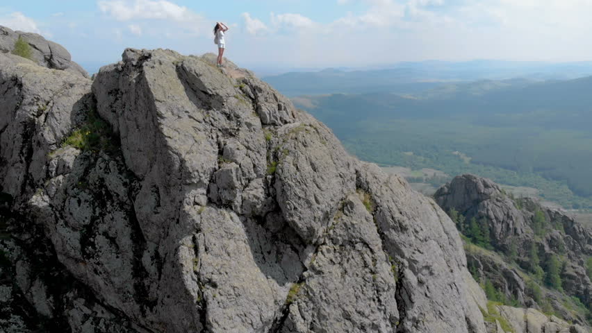 A young woman is standing on the edge of an impressive mountain cliff, dolly zoom