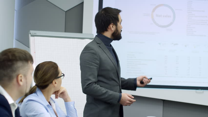 Bearded Asian businessman switching slides on whiteboard and giving business presentation to coworkers | Shutterstock HD Video #1013479406