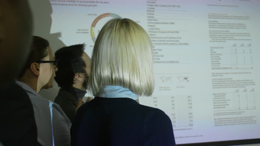 Rear view of colleagues watching business presentation projected on whiteboard and using laser pointer | Shutterstock HD Video #1013487056