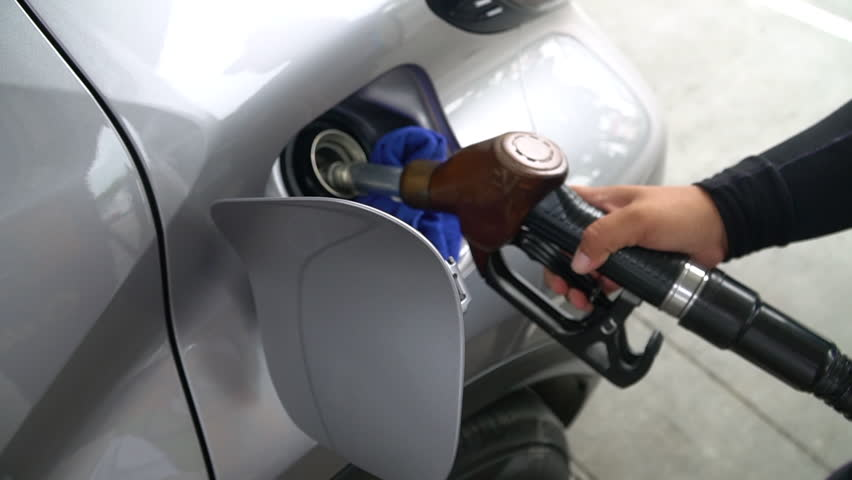 Closeup of man filling benzine gasoline fuel in car at gas station.Refuel with nozzle machine at petrol gas pump service.