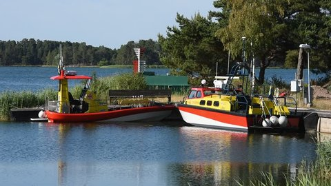 Okno, Monsteras, Sweden - June 28, 2018: Everyday scene of two search and rescue boats moored in a marina surrounded by coastal nature landscape. Late summer afternoon.