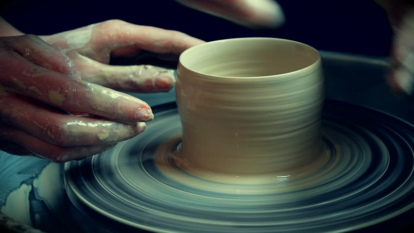 Workshop molding of clay on potter's wheel. Dirty hands in the clay. Making ceramic products. Artistic creative. Sculptor sculpts pots products from white clay. Master crock. Potter's work close-up.