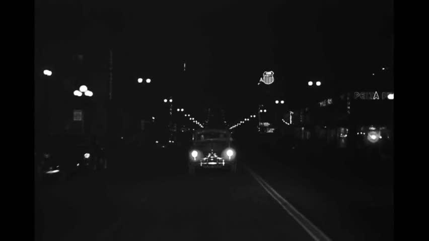 CIRCA 1946 - A camera mounted on the back of a car films a drive and turn along a Los Angeles street at night.   Shutterstock HD Video #1013544146