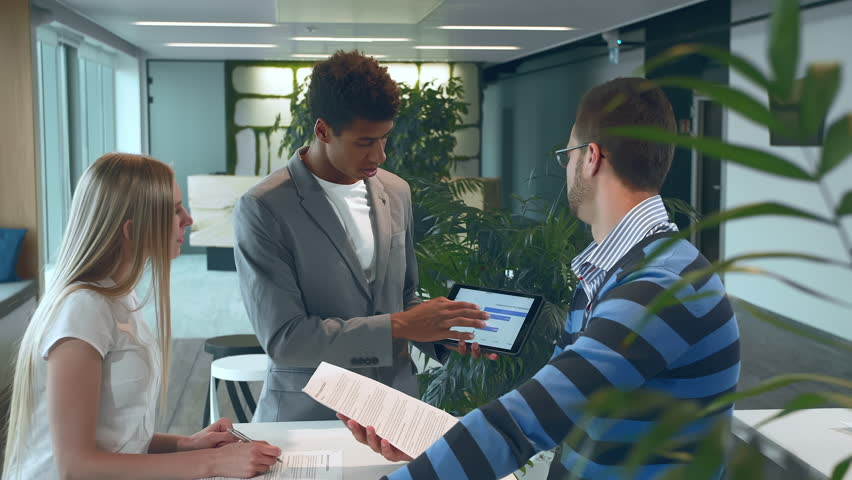 Multiracial men and woman working on report. Group of diverse woman and men with tablet in modern office hall having work with documents and statistics. | Shutterstock HD Video #1013575646