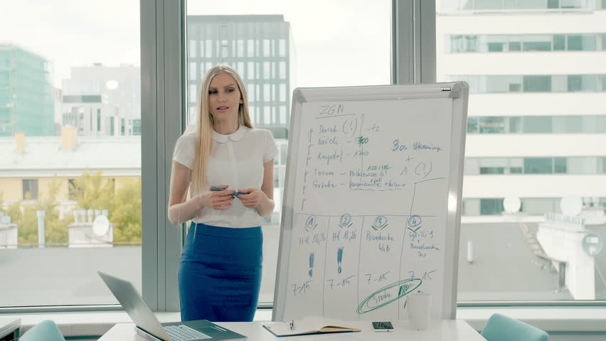 Business woman making presentation on whiteboard. Young stylish woman with long blond hair writing on whiteboard while making presentation in modern office against window. | Shutterstock HD Video #1013575796