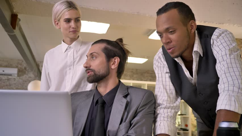 Three multy-ethnic workers discuss idea on laptop, coworking concept, communication concept | Shutterstock HD Video #1013617106