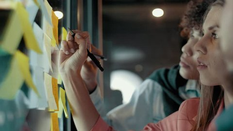 Cheerful european woman writing notes on sticky multicolored stickers at transparent glass wall multiethnic creative business team brainstorming analyzes concept planning strategy of start up project