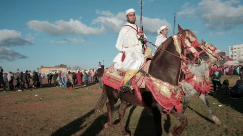 Meknes, Morocco - March 31, 2018: Tracking right pan follow Moroccan tribesmen competitors with rifles on horseback passing after competing in Tbourida or Fantasia competition