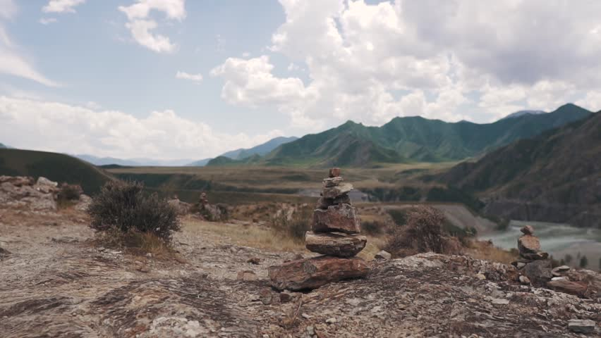 Woman tourist makes a pyramid of stones. traveler in the mountains | Shutterstock HD Video #1013629166