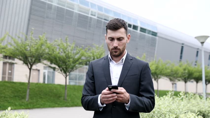 Handsome Confident Businessman Walking through the Park in the City. Wearing Classical Suit. Using his Mobile Phone.  | Shutterstock HD Video #1013630786