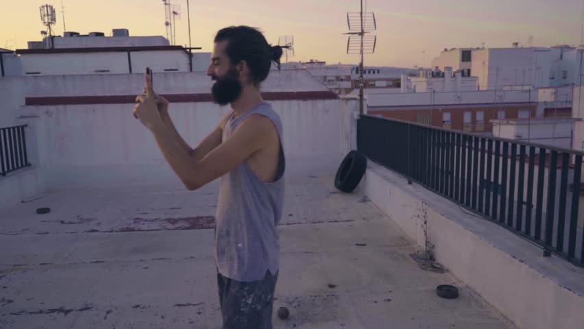 Man taking a picture with mobile at sunset on a rooftop | Shutterstock HD Video #1013668826
