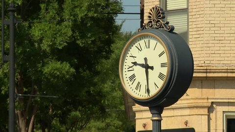 A clock on Main Street in the downtown shopping district in a small town in the Midwest.