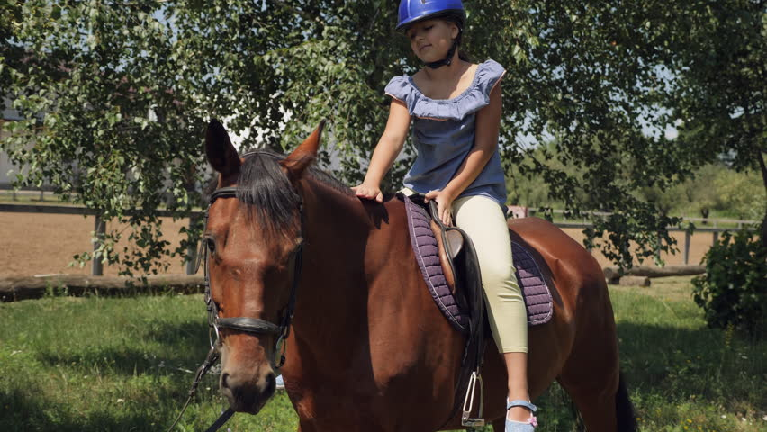 A young girl caresses a horse while riding. A little girl is sitting on a horse in a helmet | Shutterstock HD Video #1013677016