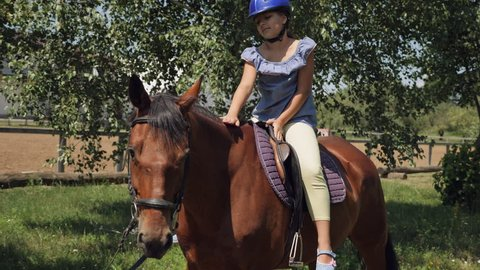 A young girl caresses a horse while riding. A little girl is sitting on a horse in a helmet