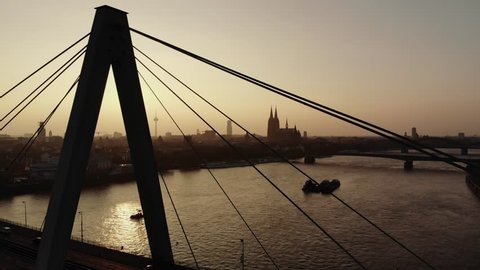 The sun sets over Cologne and makes the silouette appear orange. The cathedral and the Severinsbrücke are in focus.