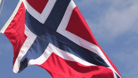 Sunlit Norwegian flag waving in the wind against a hazy blue sky