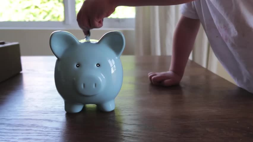 Close up footage of a youg childs hand putting money into a blue piggy bank   Shutterstock HD Video #1013704736