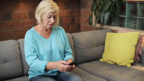 Caucasian old lady with backache touching pain place. Unhappy woman standing from gray sofa. Indoors. Lifestyle. Close-up.