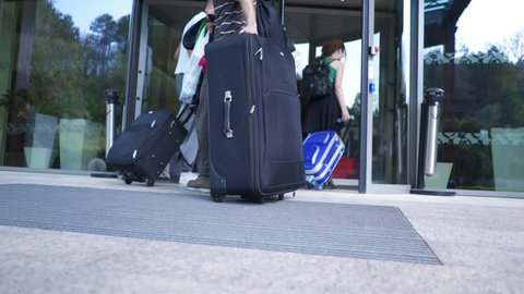 Travellers carrying luggage through revolving door. Group of tourists with suitcases entering the station through glass doors.