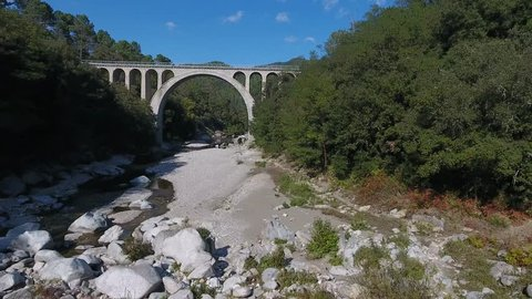 Flying under a bridge with small river in south of France. Sunny day.