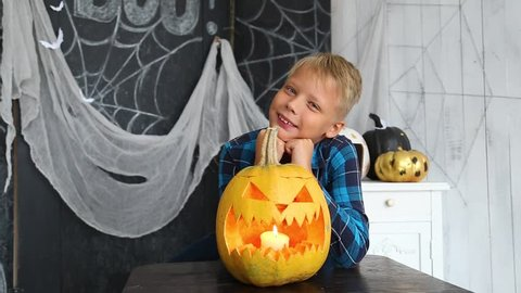 Portrait of cute smiling kid with orange pumpkin at Halloween celebration. Boy posing for photo happily, looks at camera. Real time full hd video footage.