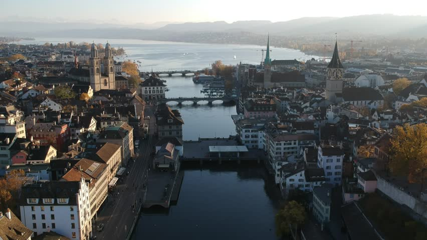 Aerial drone shot flying over the river Limmat in Zurich at sunset with lake Zurich in the background