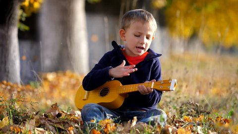 Portrait of funny child sing at guitar, happy kid clapping his hands in park