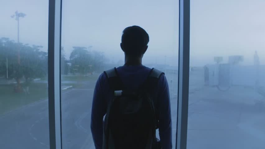 Dramatic shot of a young man looking out an airport window | Shutterstock HD Video #1013785286