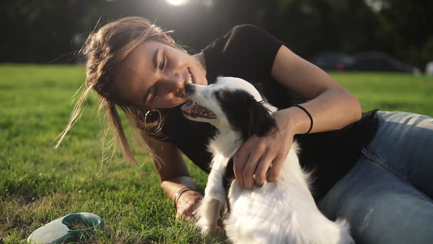 Smiling lady taking free time with her dog. Woman relaxing in the nature with her little dog. Scratching her back. Dog licking her owner nose. Close up