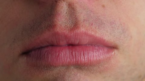 Man lick his lips. Closeup on mouth