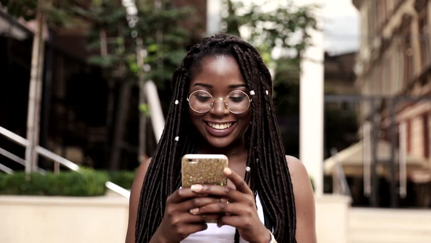 Portrait of Young Afro-american Girl Walking in the City. Happily Smiling Woman with Braids. Using her Smartphone. Wearing Round Eye Glasses.