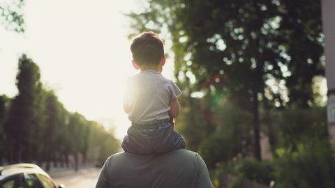 Father and son walking in city at sunset. Two year old kid is sitting on the parent's shoulders. Happy family concept