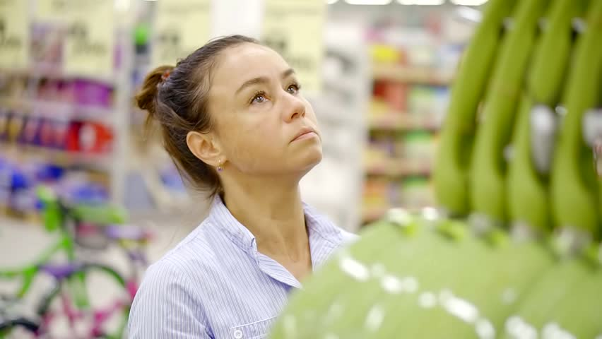Middle aged brunette female shopper is choosing frying pan in a supermarket, standing near stands | Shutterstock HD Video #1013819276