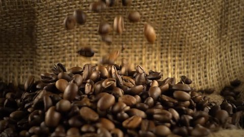 Coffee beans falling on heap of coffee beans on burlap sack in slow motion