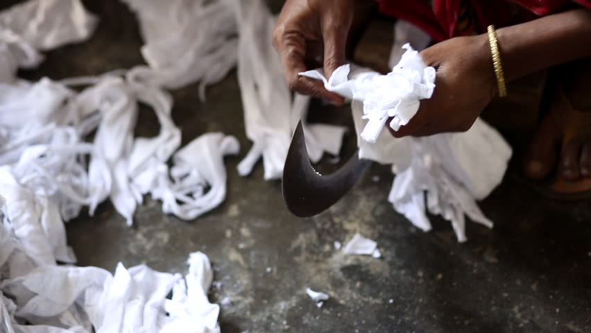 Bangladesh worker cutting strips of cotton fabric on curved blade