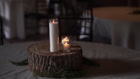Reception table centerpiece that consists of burning candles on a wood block.