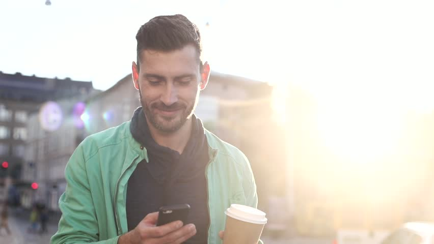 Handsome Bearded Man Walking in the Wide Street at Sunset. Drinking Coffee to go. Using his Mobile Phone. Enjoying the Evening Walk. Man Walking in the Crowded Street full of Cars. | Shutterstock HD Video #1013876846