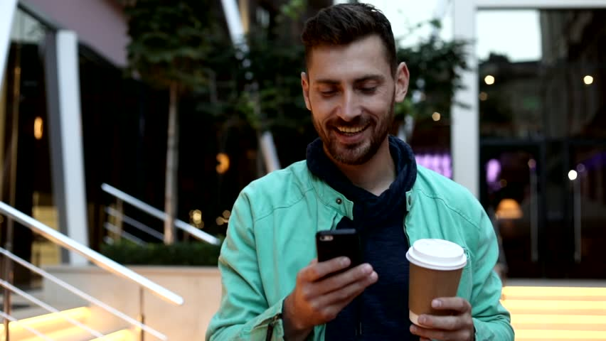 Happy and Satisfied Man Walking Down the Street. Holding a Paper Cup with Black Coffe. Typing a Message on his Smartphone. Big Glass Buildings on the Background. Casual Outfit. | Shutterstock HD Video #1013876876