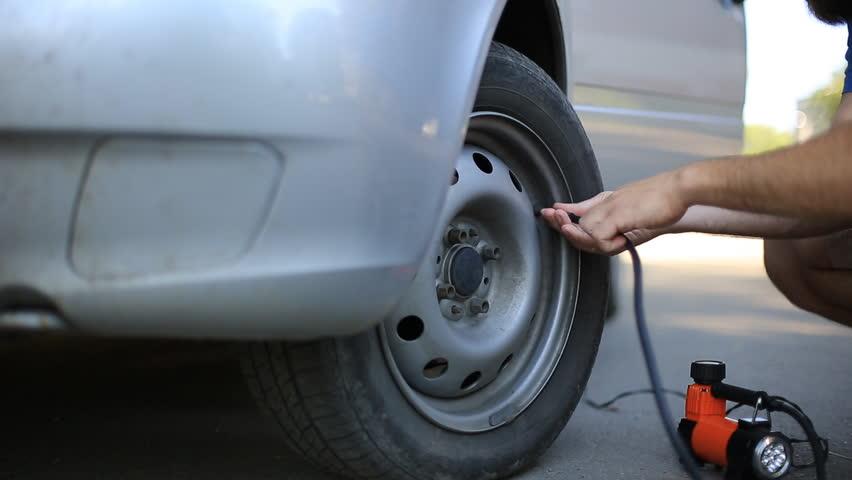 Man compressor pump pumps the front wheel of the car. | Shutterstock HD Video #1013877356
