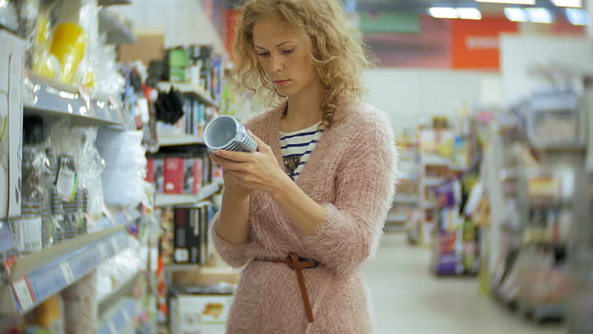 Young woman stands near the supermarket shelf and selects the products 4k | Shutterstock HD Video #1013883866